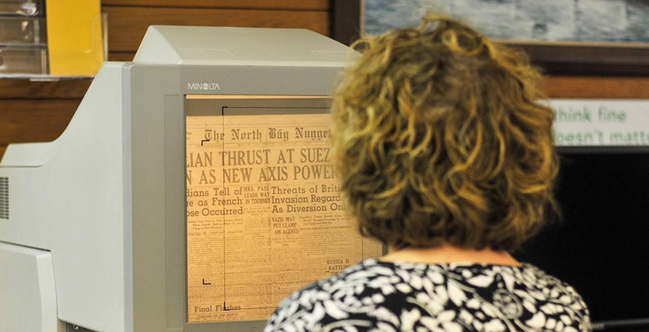A woman reads an old issue of the North Bay Nugget on microfilm