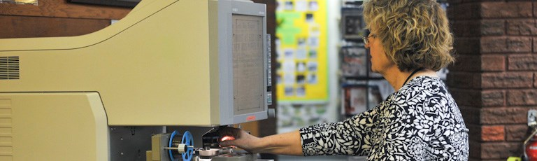 A woman using a microfilm viewer.