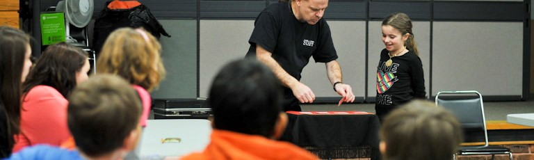 A young girl assists with a demonstration at a library event.