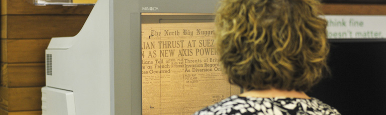 A woman using a microfilm viewer